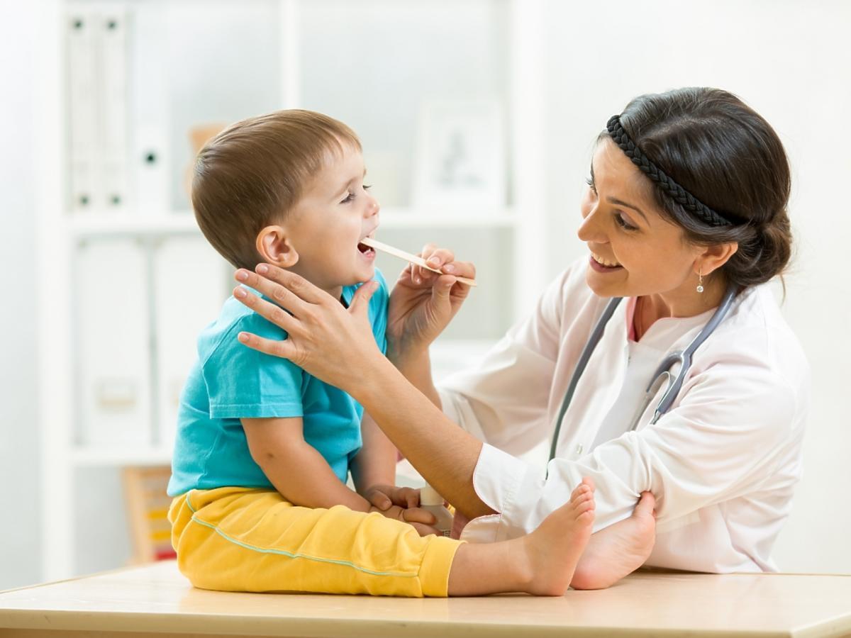 Lekarz bada dziecku gardło