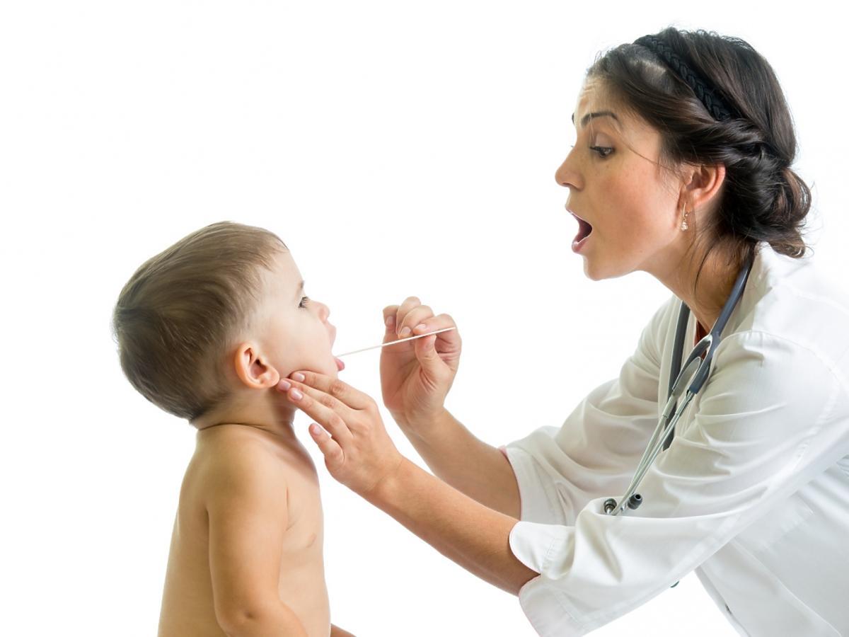 Lekarz bada gardło dziecku