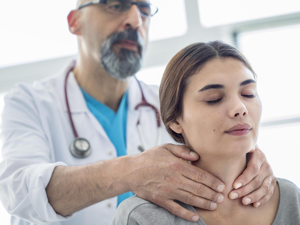 lekarz bada tarczycę kobiety