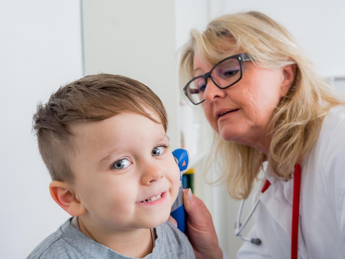 Lekarz bada ucho chłopcu.