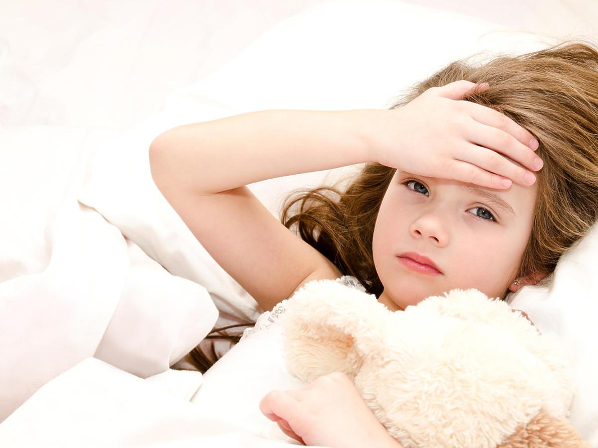 leżąca w łóżku dziewczynka trzymająca się za czoło
