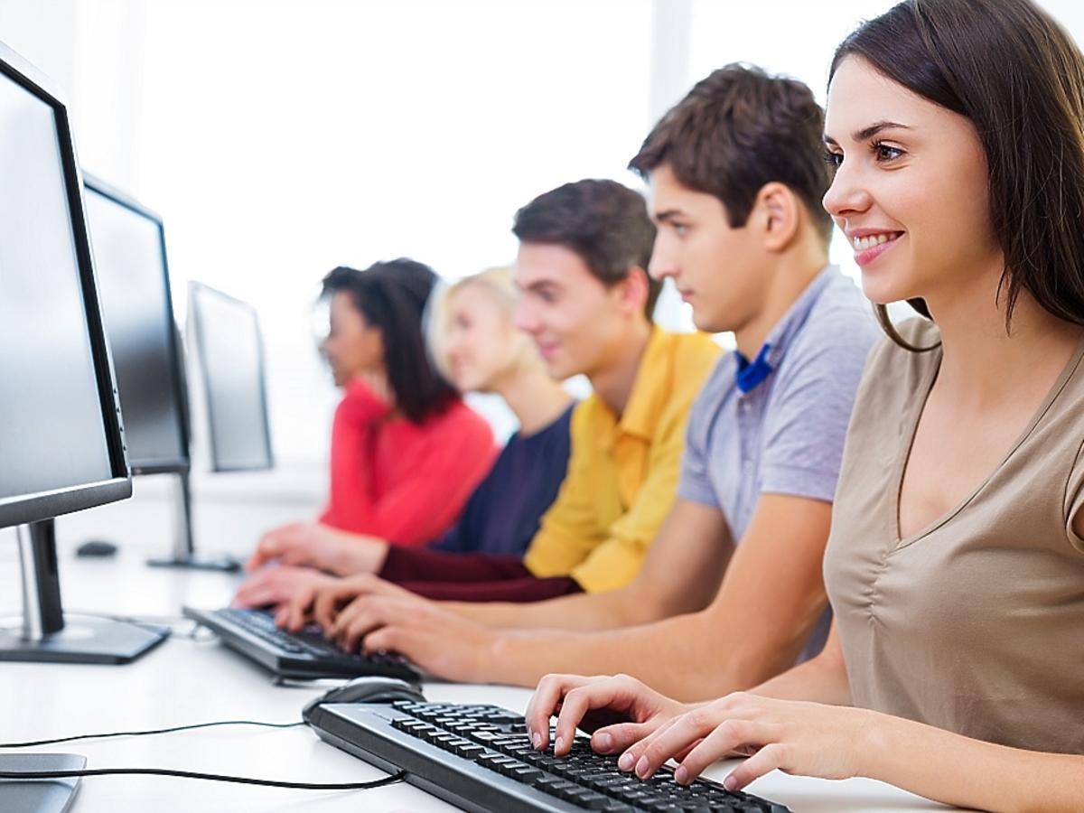 ludzie siedzący w rzędzie przed komputerami