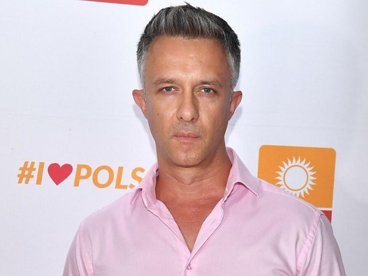 Łukasz Płoszajski w różowej koszuli