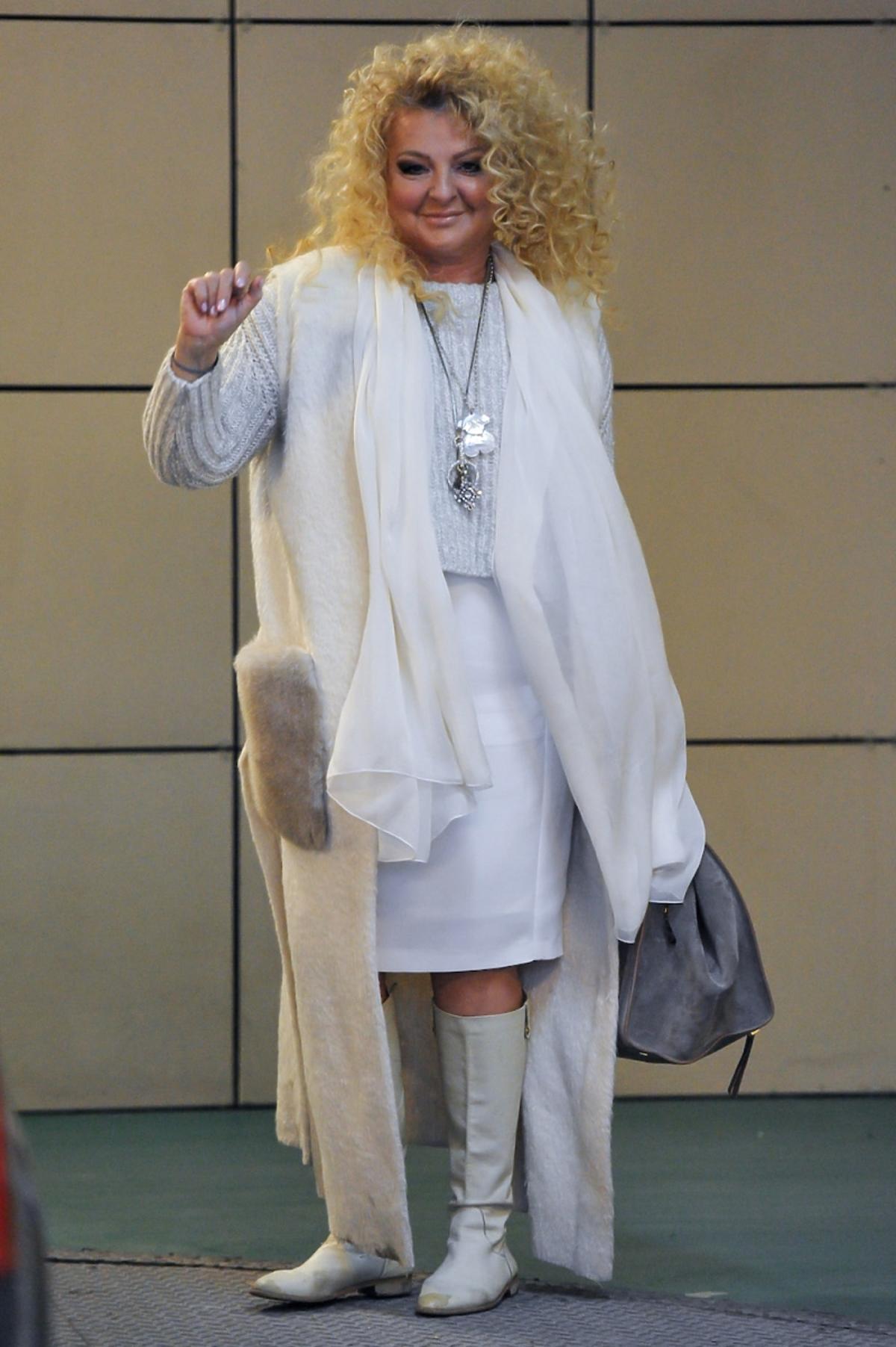 Magda Gessler w białym zestawie z szarą torbą