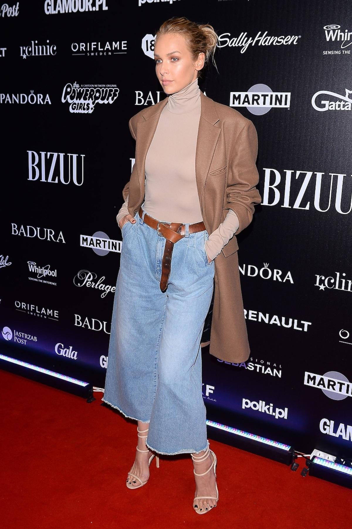 Magdalena Mielcarz w dżinsach, płaszczu i z paskiem