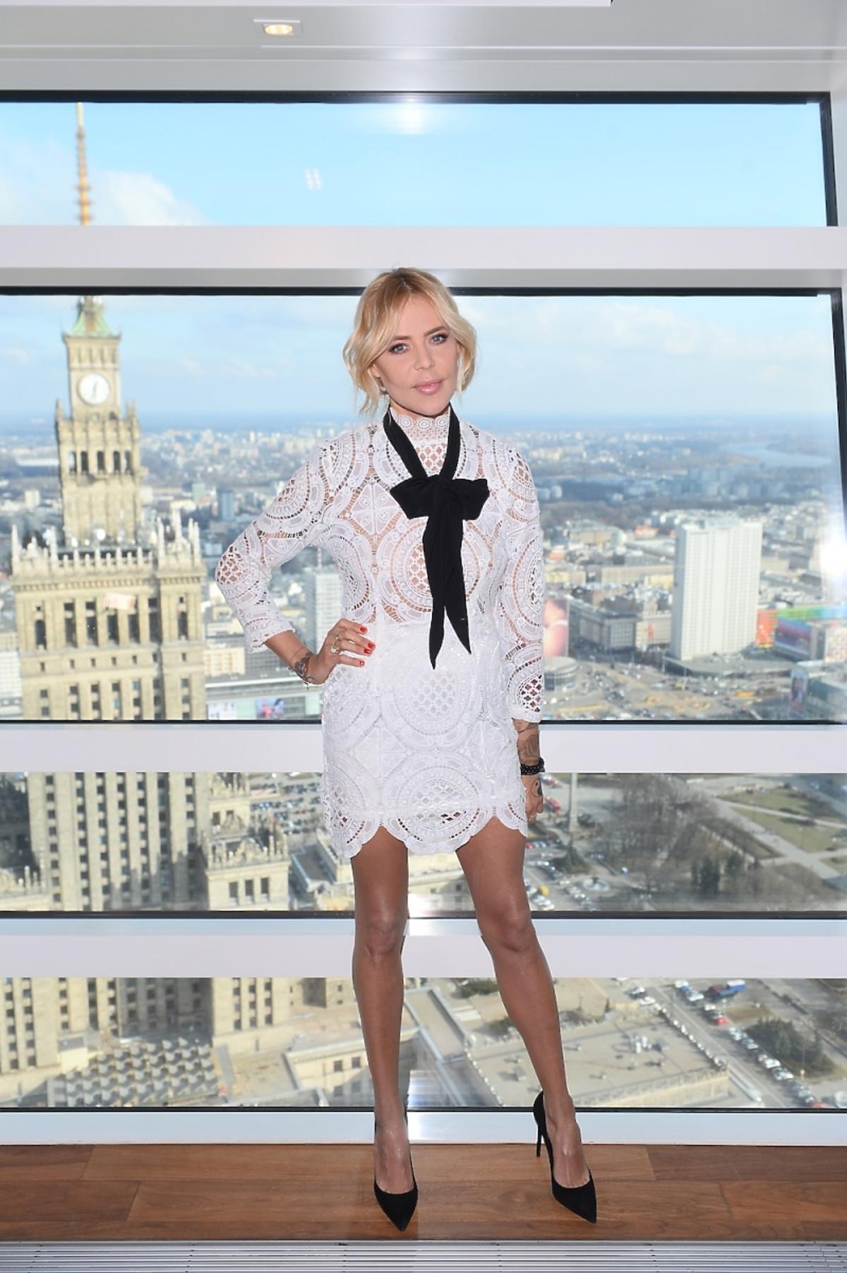 Maja Sablewska w białej koronkowej sukience z kokardą na tle panoramy Warszawy