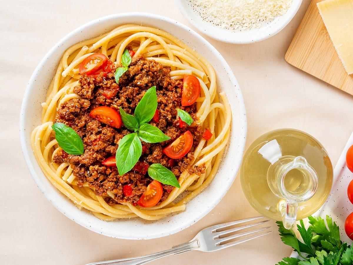 makaron z mięsem mielonym, sosem pomidorowym, bazylią i serem na białym talerzu