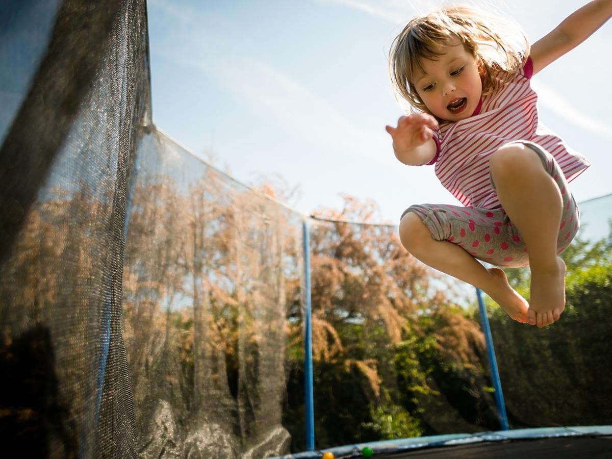 Mała dziewczyna skacze po trampolinie ogrodowej.