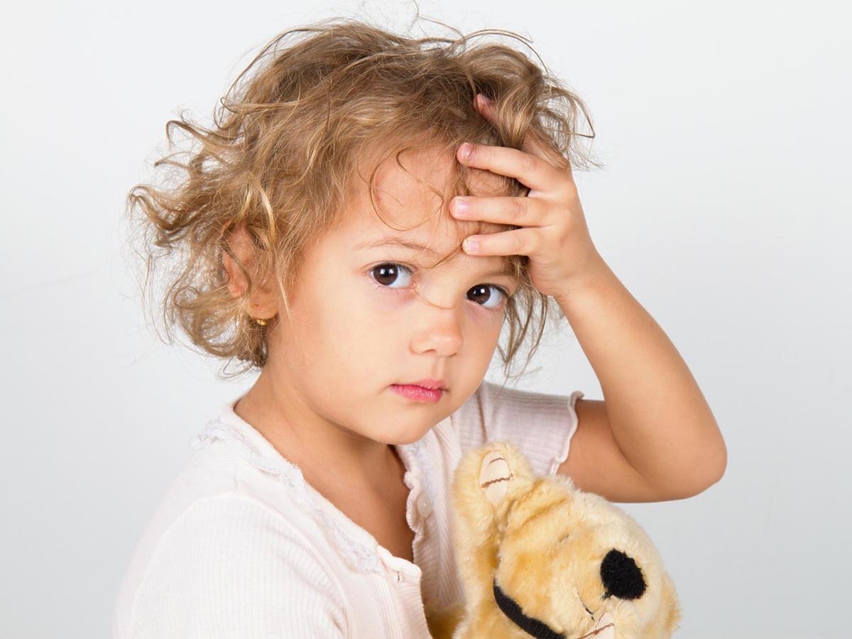 Mała dziewczynka trzyma się za głowę.