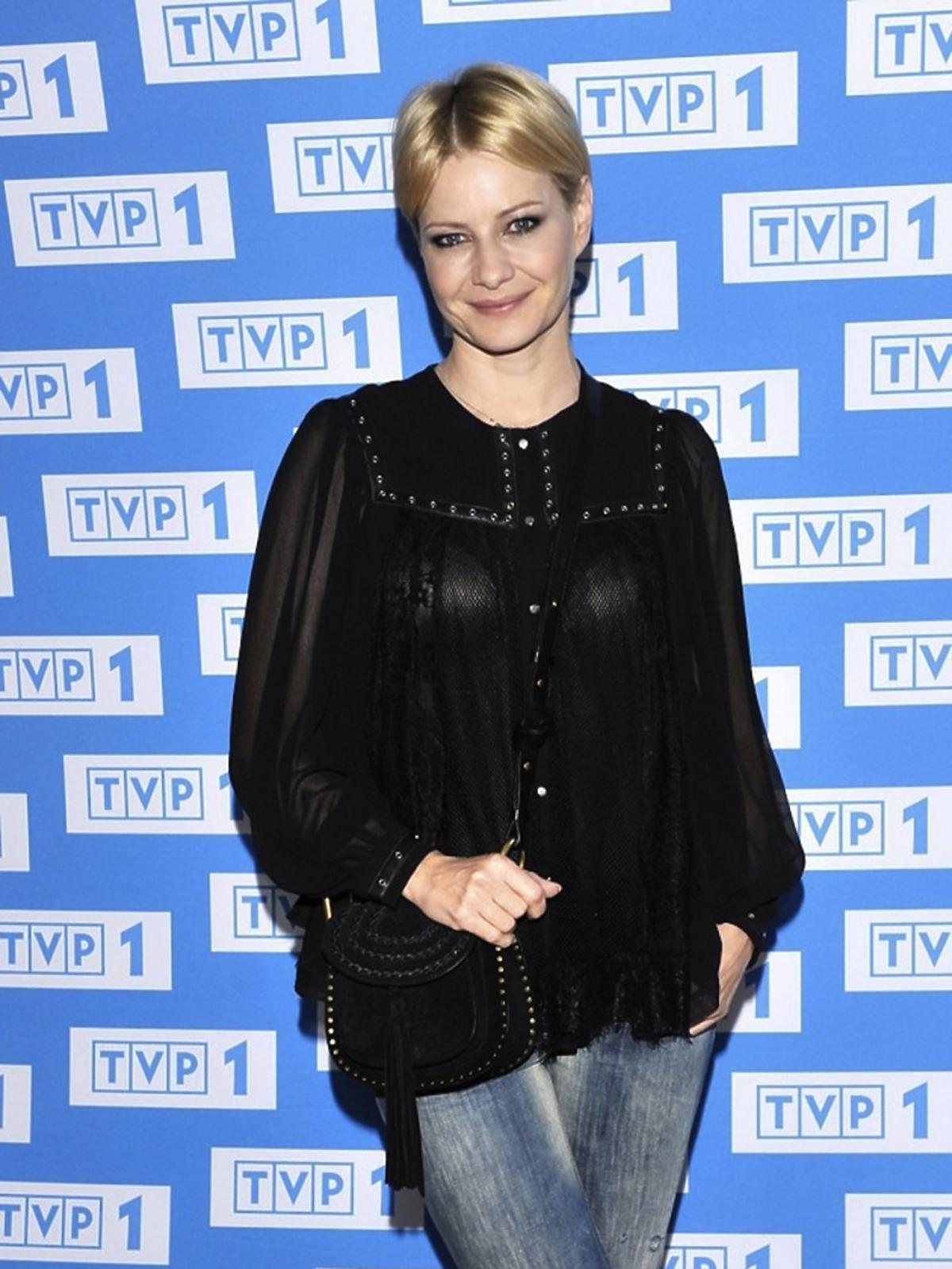 Małgorzata Kożuchowska w czarnej bluzce, dżinsowych dzwonach