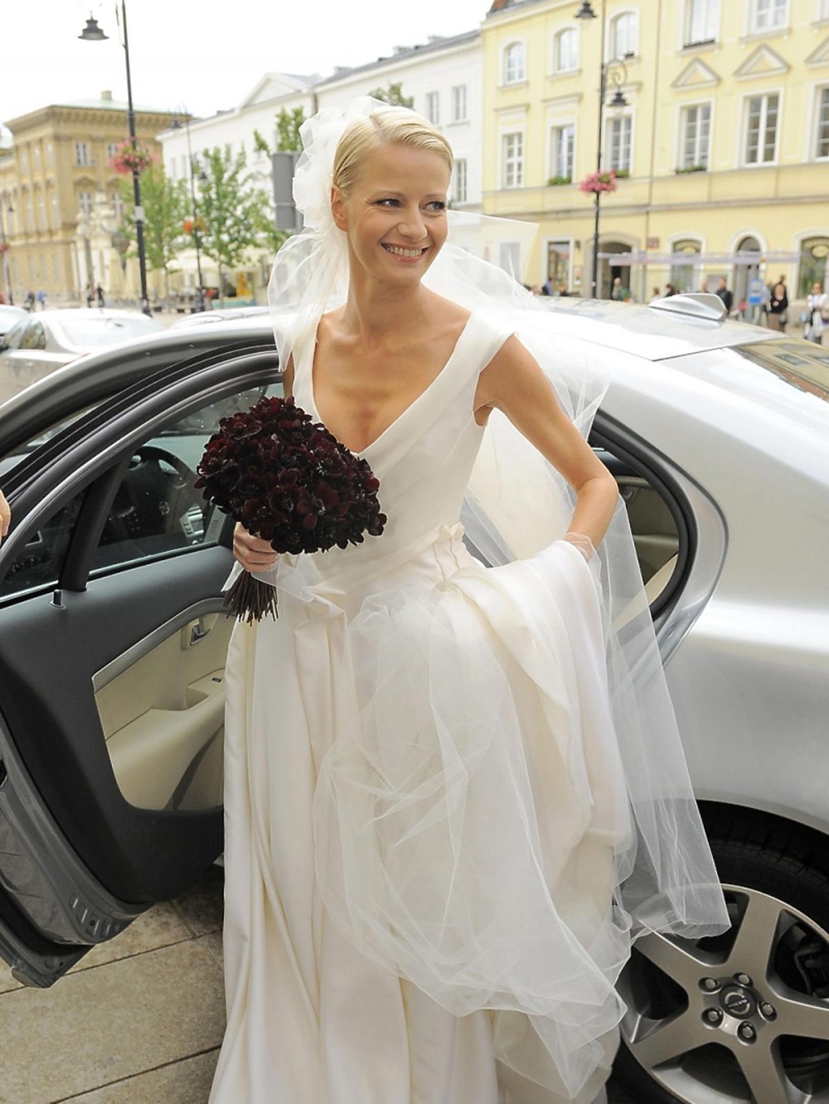 Małgorzata Kożuchowska w sukni ślunej z welonem i bukietem kwiatów