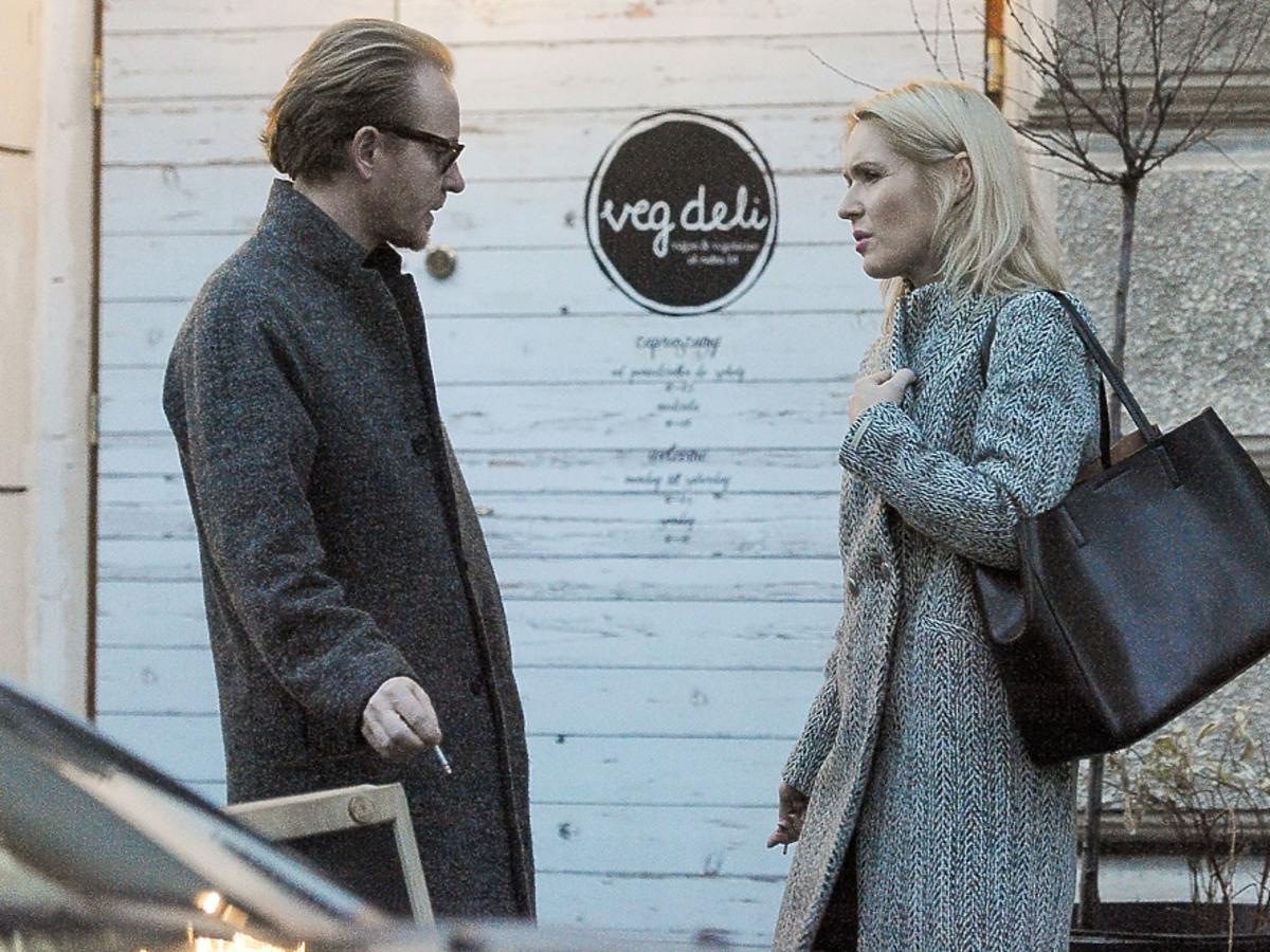 Małgorzata Ohme w szarym plaszczu i Jacek Borcuch w czarnym płaszczu razem palą papierosa