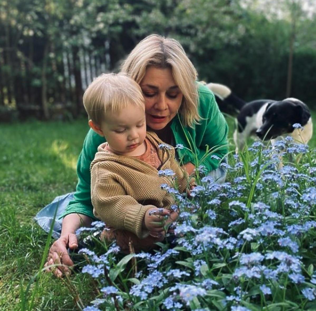 Małgorzata Ostrowska-Królikowska pokazuje wnukowi kwiaty
