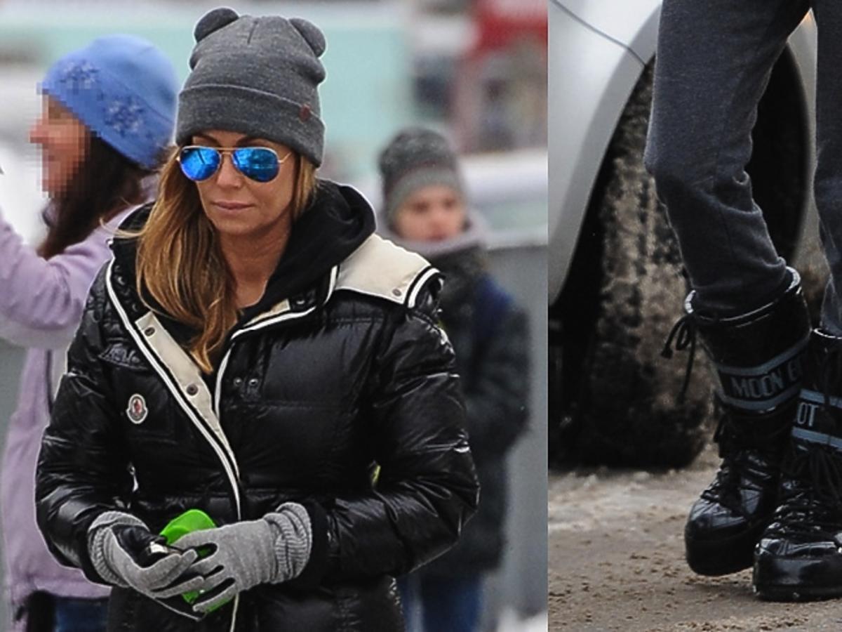 Małgorzata Rozenek w czarnej kurtce, szarych spodniach i czapce, niebieskich okularach