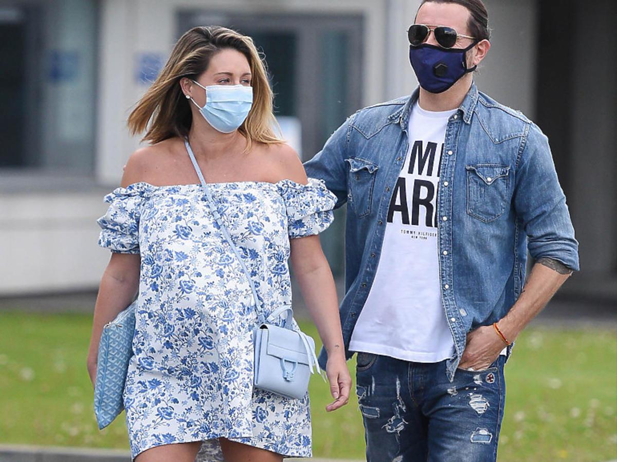 Małgorzata Rozenek w kwiecistej sukience i Radosław Majdan pod szpitalem