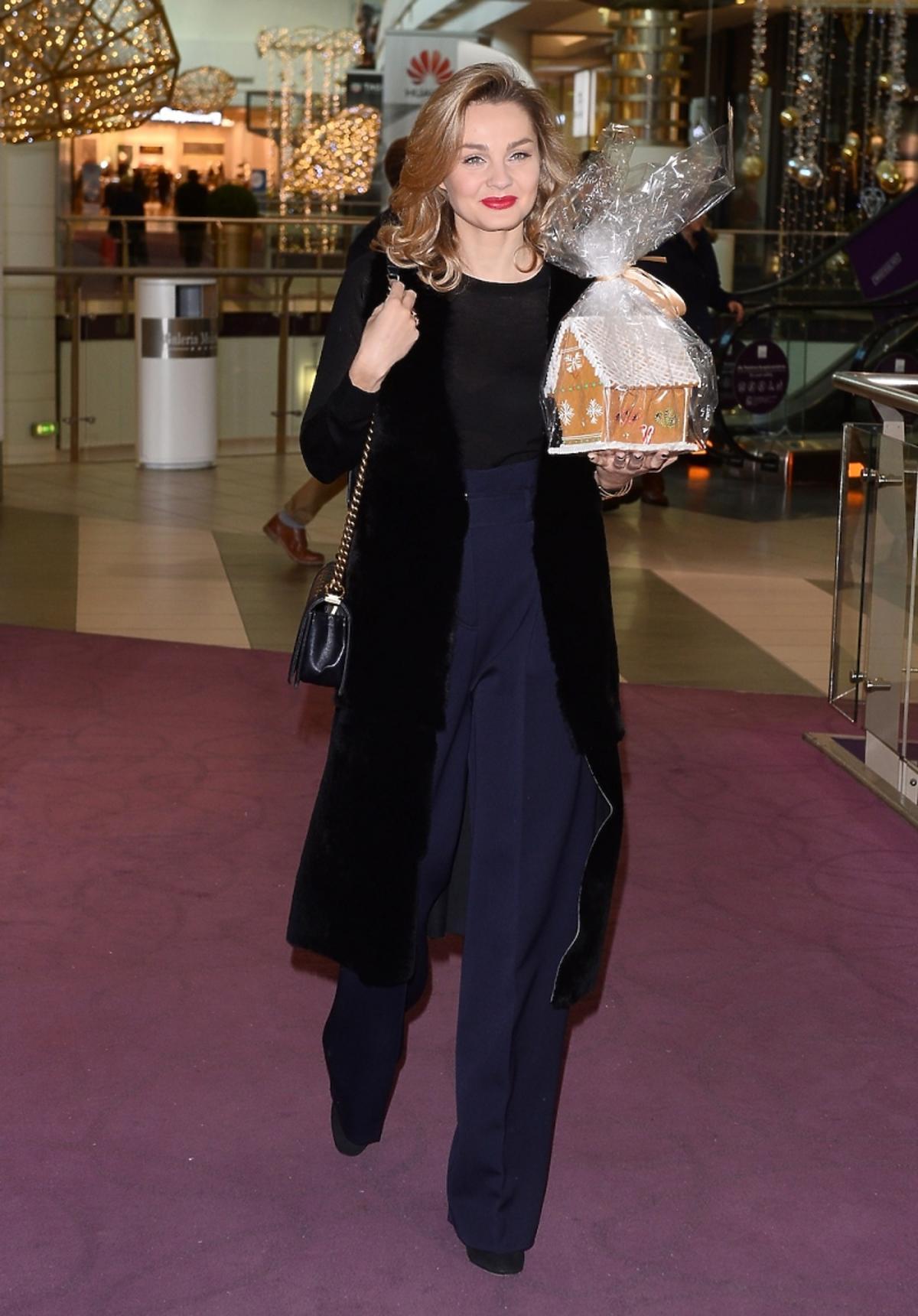 Małgorzata Socha w szerokich granatowych spodniach i czarnej długiej kamizelce z ciastem
