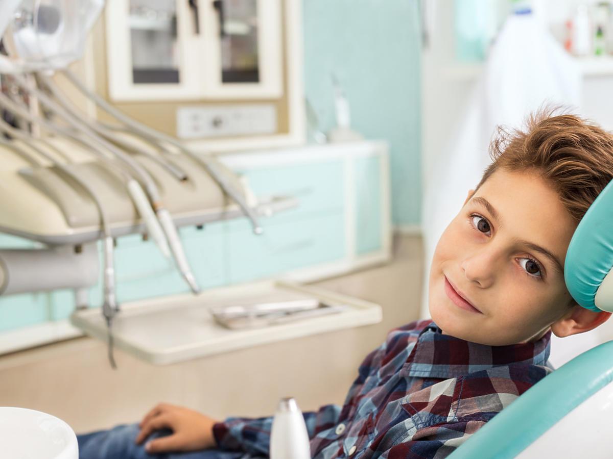 Mały chłopiec siedzi na fotelu u dentysty.