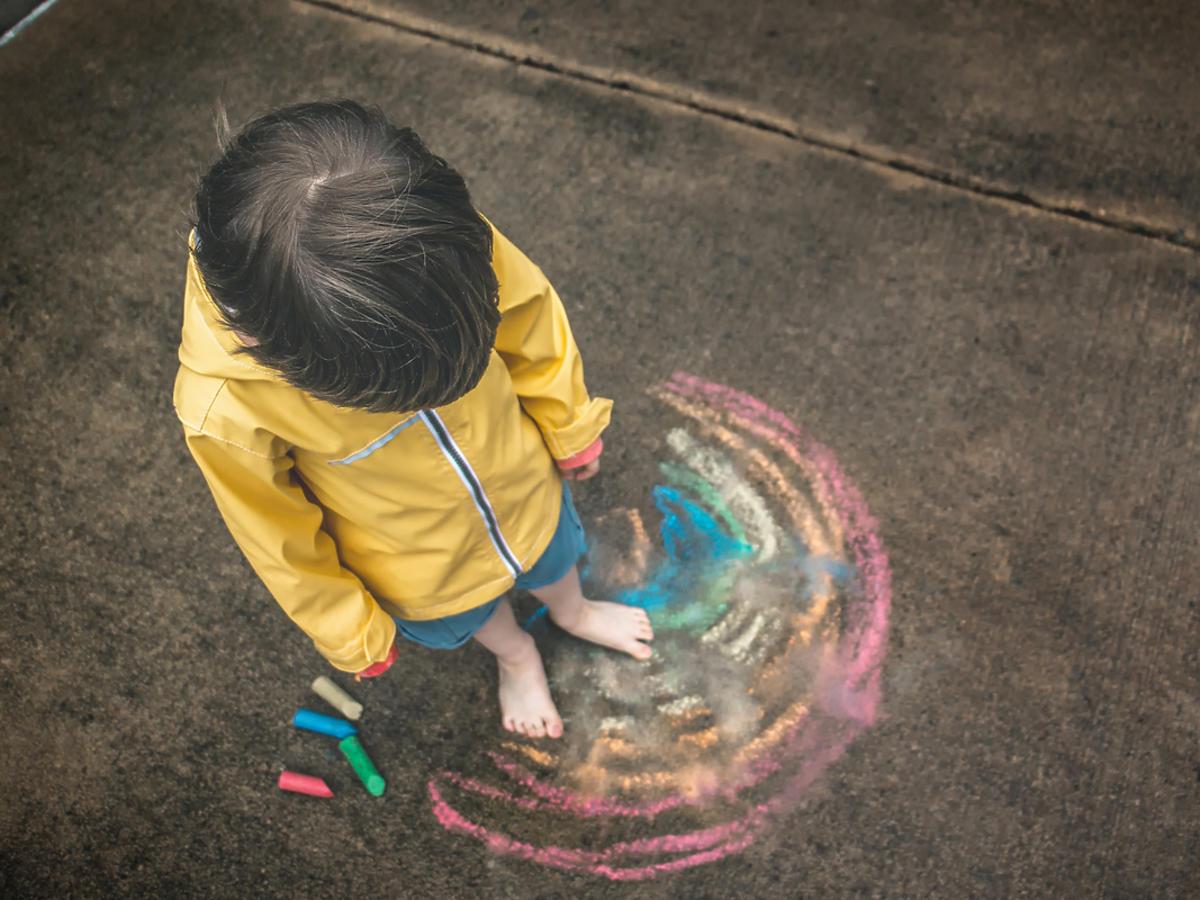 Mały chłopiec w płaszczu przeciwdeszczowym przygląda się podłodze.