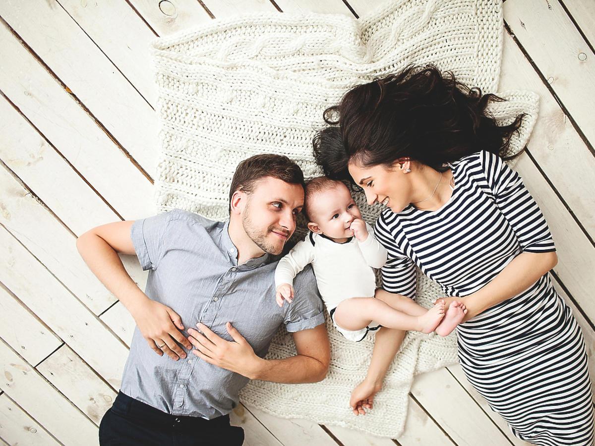 Małżeństwo leży na dywanie obok swojego dziecka