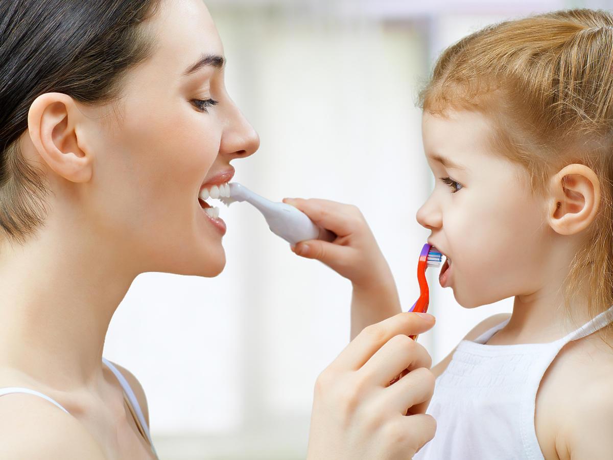 Mama i córka szczotkują sobie nawzajem zęby