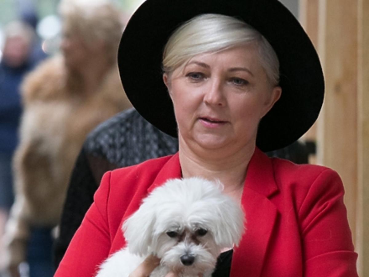 mama Margaret Elżbieta Jamroży w czerwonej marynarce, czarnym kapeluszu i z psem na ulicy
