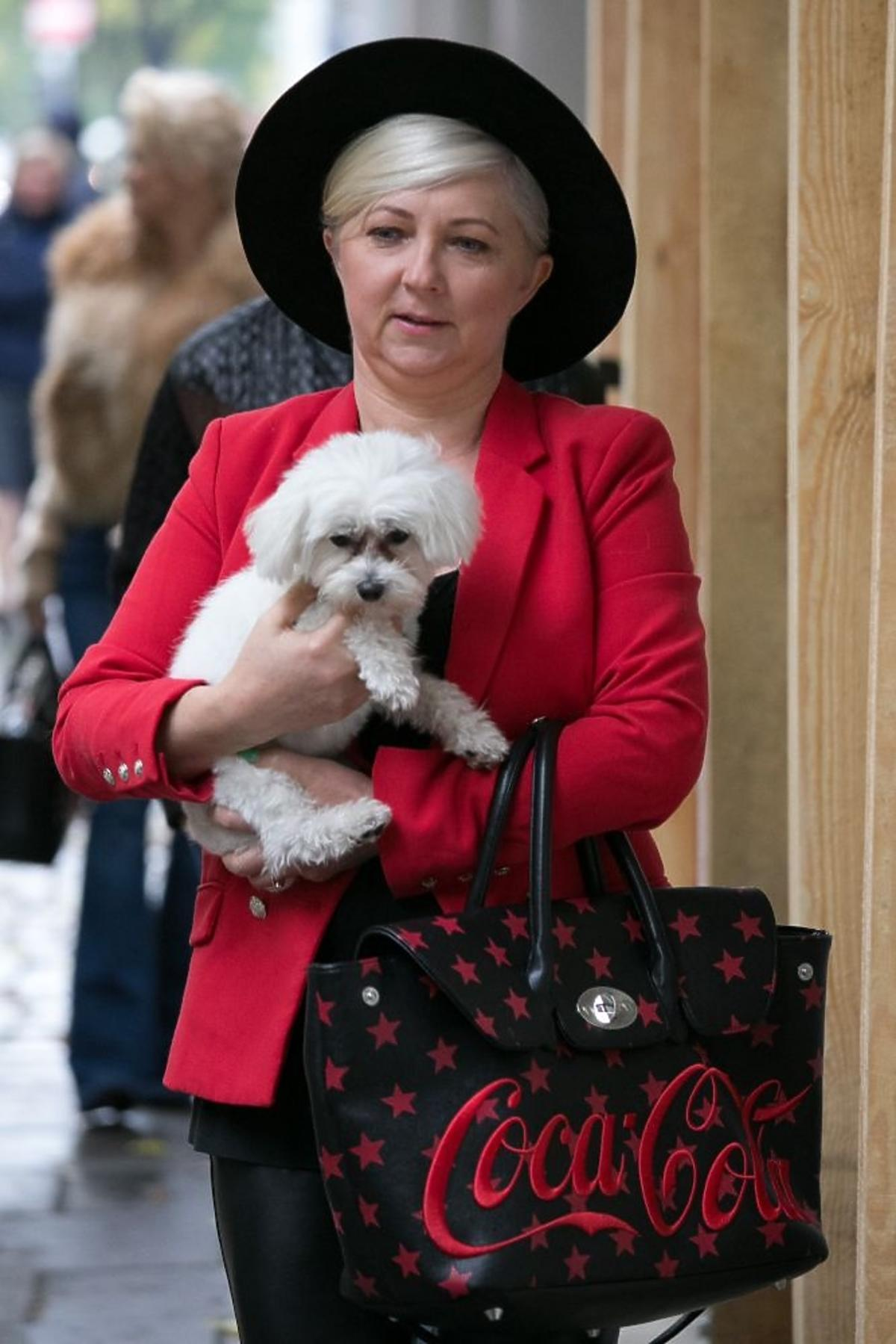 Mama margaret w kapeluszu i czerwonej marynarce na ulicy z psem