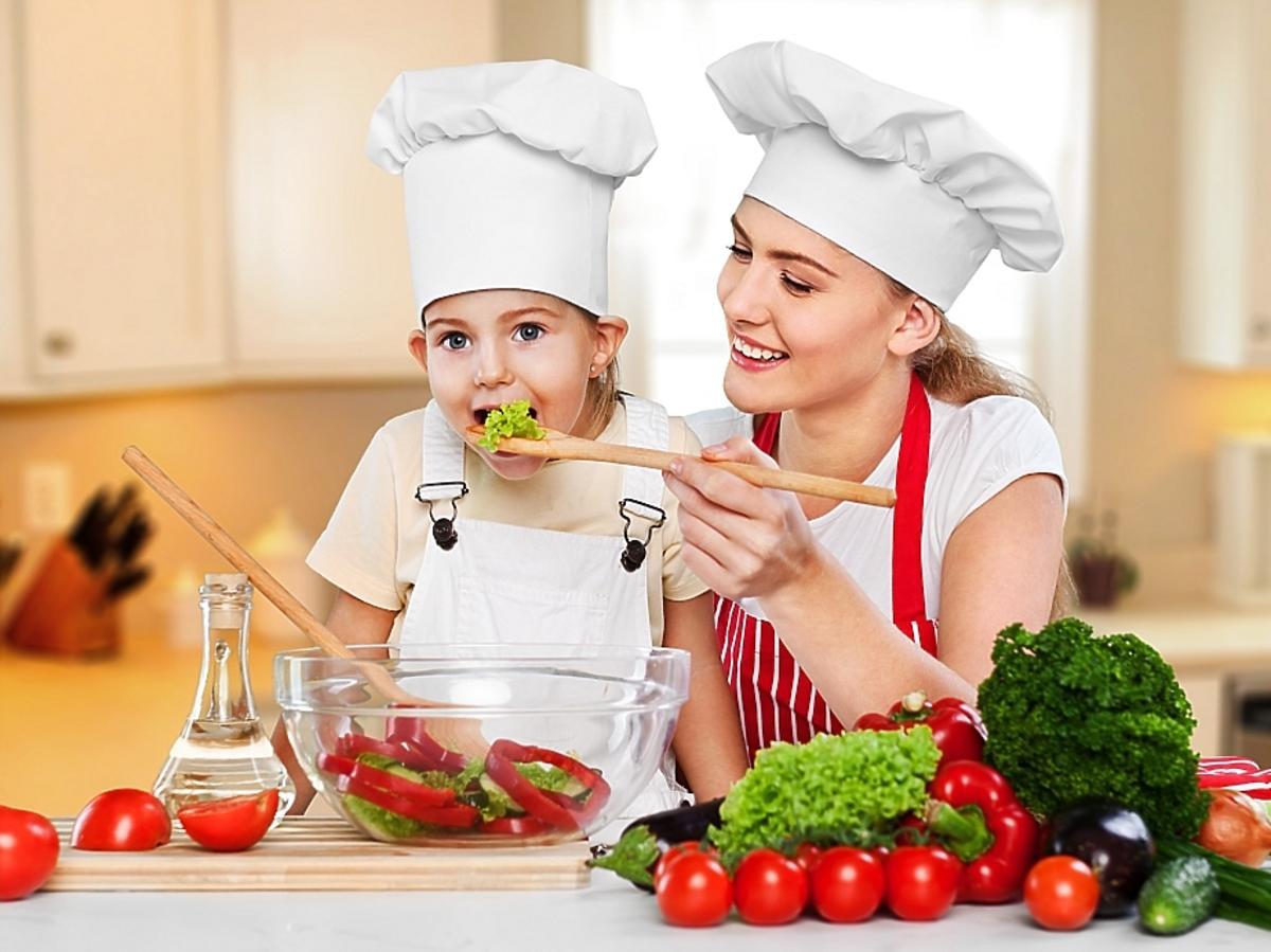 Mama z dzieckiem przyrządza potrawę z wielu warzyw