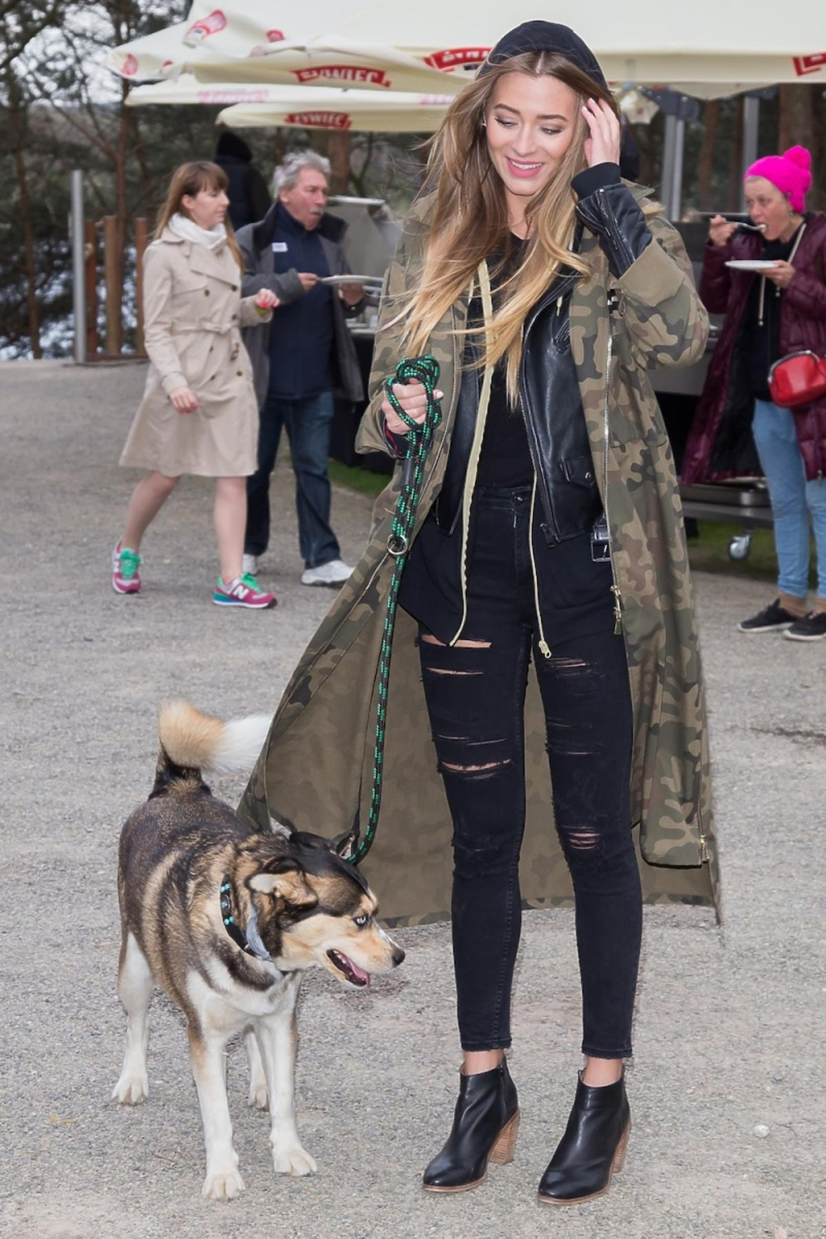 Marcelina Zawadzka w kurtce moro, czarnych spodniach i z psem na smyczy