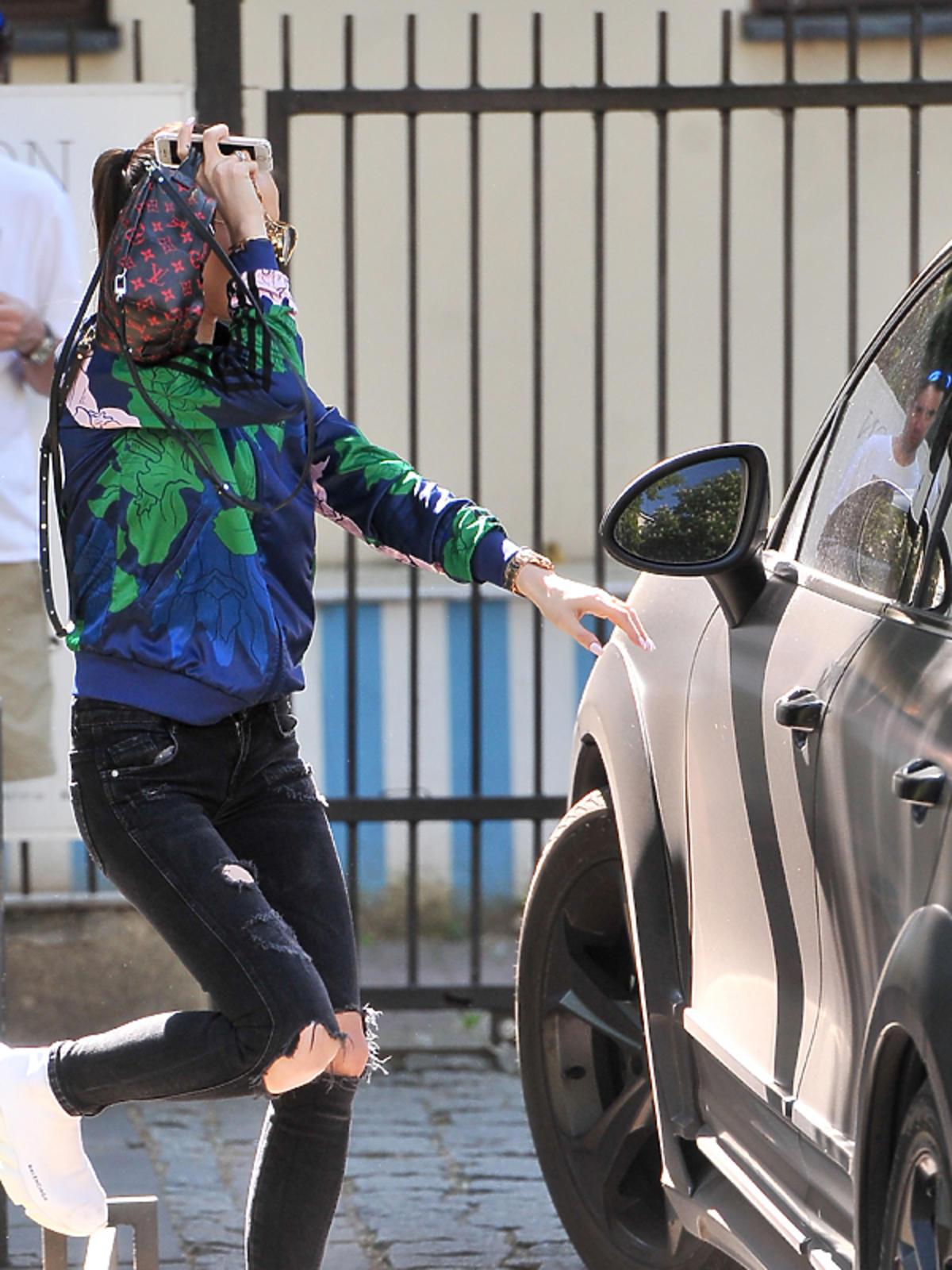 Marina wchodzi do samochodu Porsche
