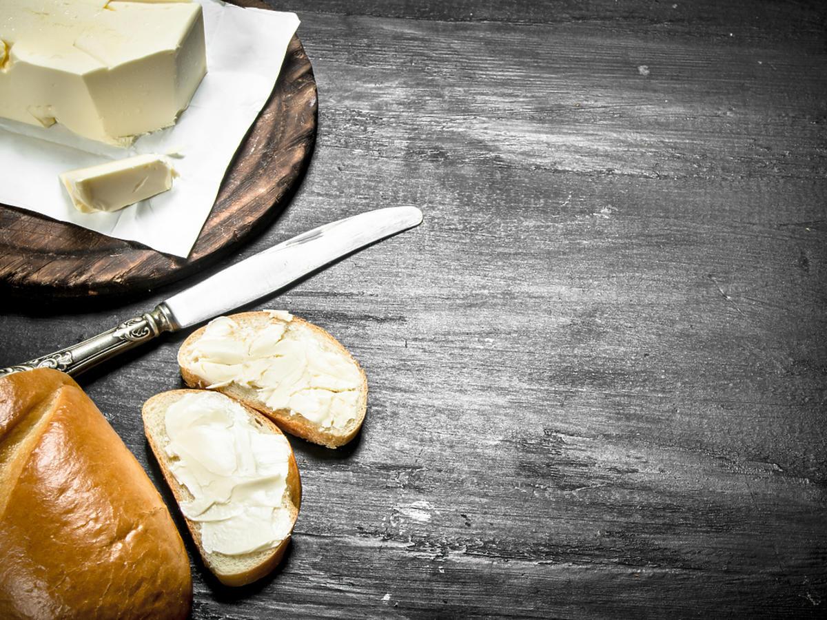 Masło pokrojone na kawałki podane jest na stole.