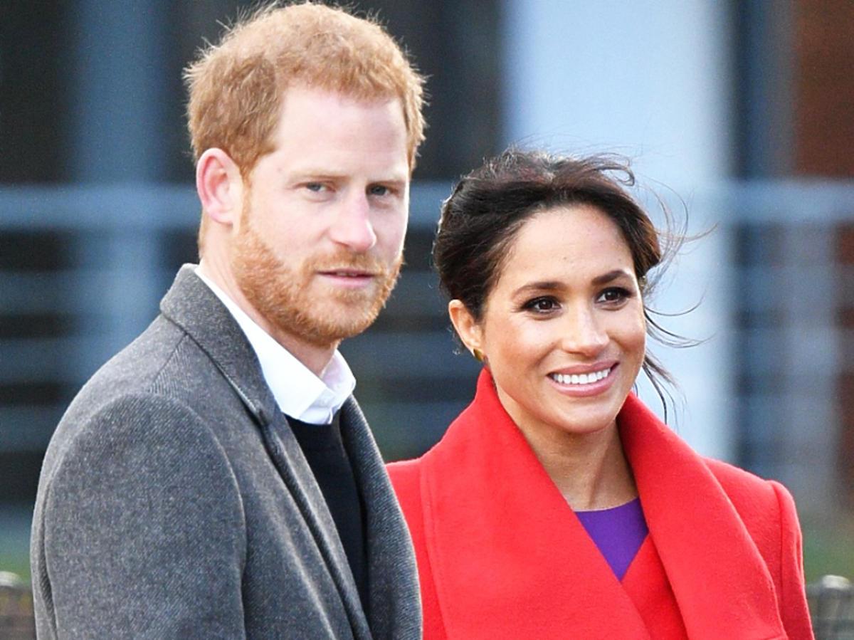 Meghan Markle w czerwonym płaszczu z księciem Harrym