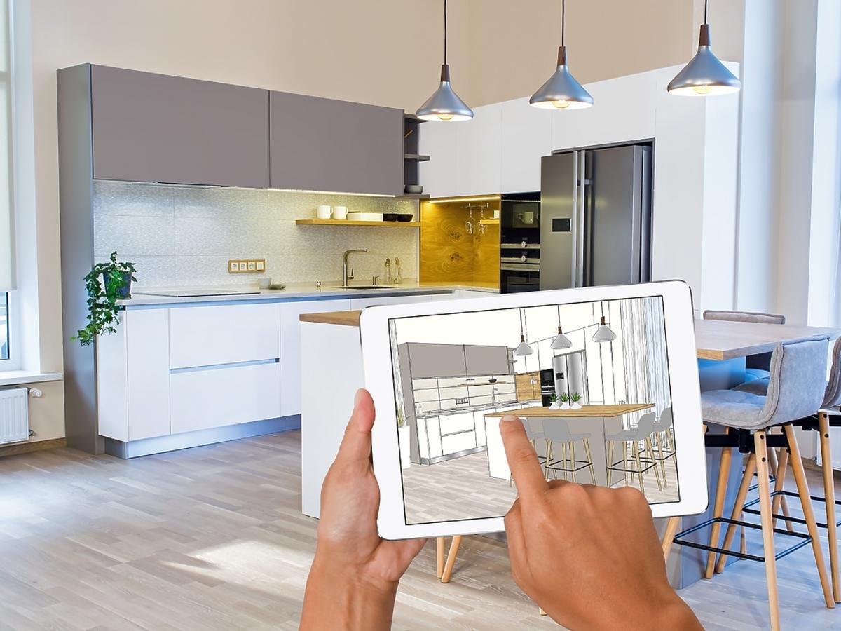 męska ręka przesuwająca palcem po ekranie tabletu z wyświetlonym planem kuchni, w tle meble kuchenne