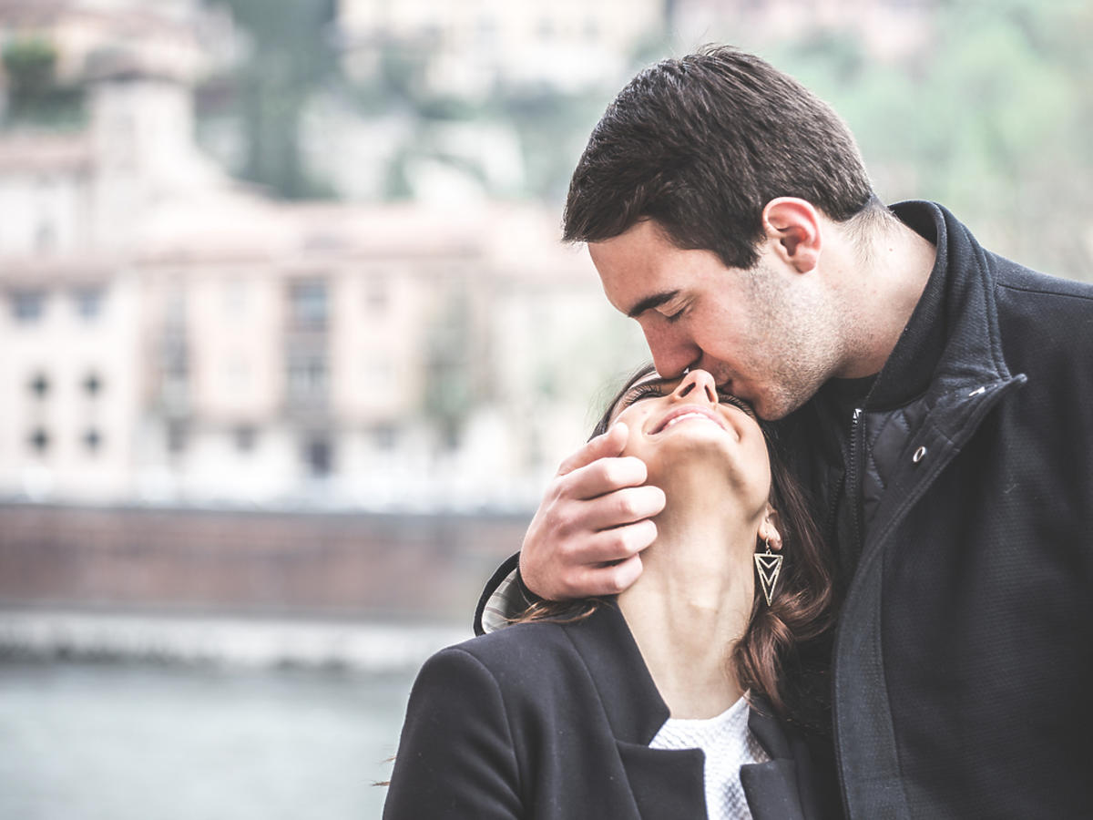 mężczyzna całujący partnerkę w czoło