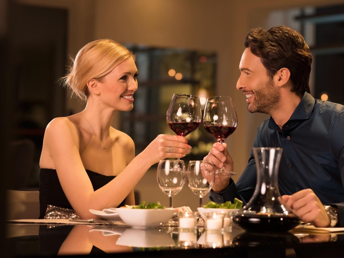 mężczyzna i kobieta w restauracji piją białe wino