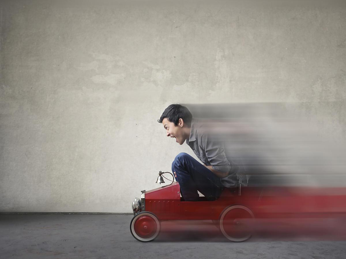 Mężczyzna jadący małym samochodzikiem zabawką