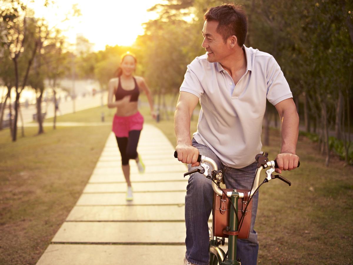 Mężczyzna jedzie na rowerze, a kobieta biegnie.