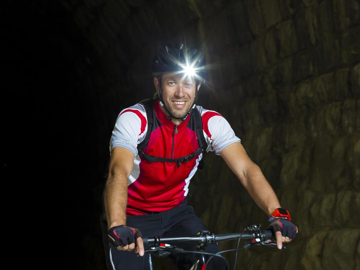 mężczyzna na rowerze z latarką na głowie