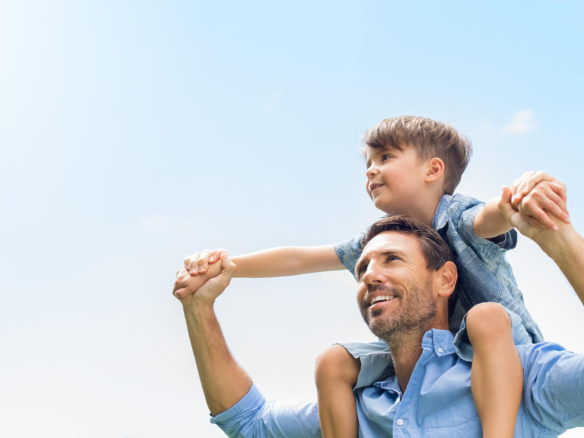 Mężczyzna niosący swojego syna na barana.