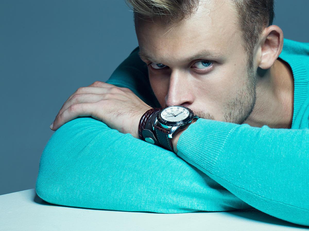 Mężczyzna o niebieskich oczach, podpiera dłonie o stół.