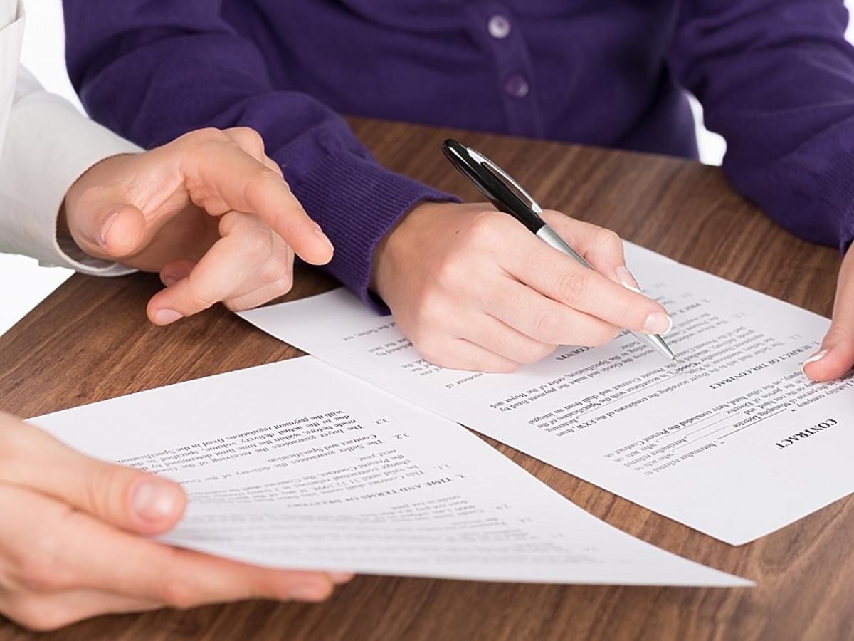 mężczyzna podpisuje dokument
