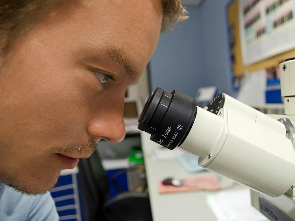 Mężczyzna przed mikroskopem