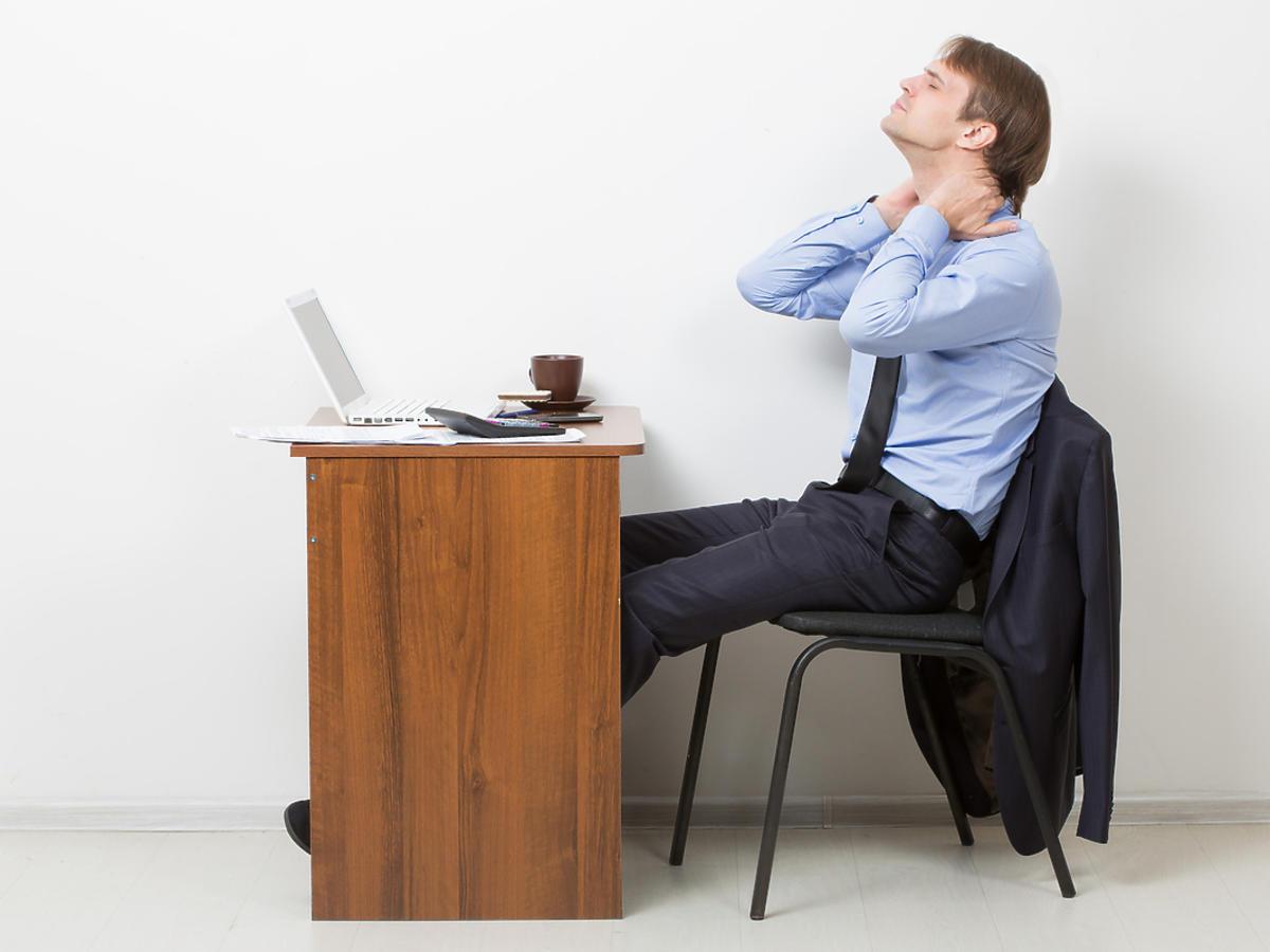 Mężczyzna siedzący przy biurku ze skurczem mięśni