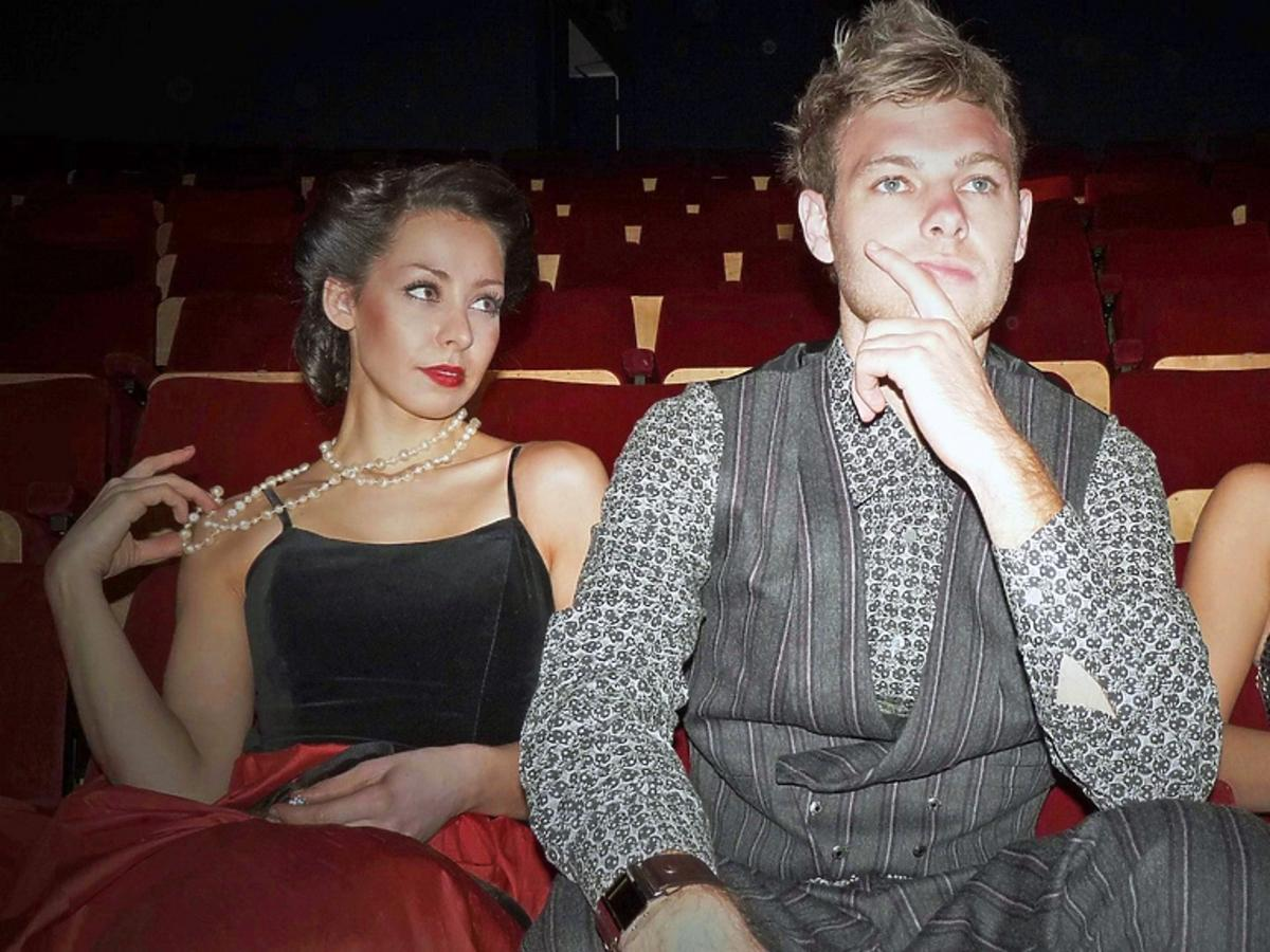Mężczyzna siedzi między dwiema kobietami. Obie na niego patrzą.