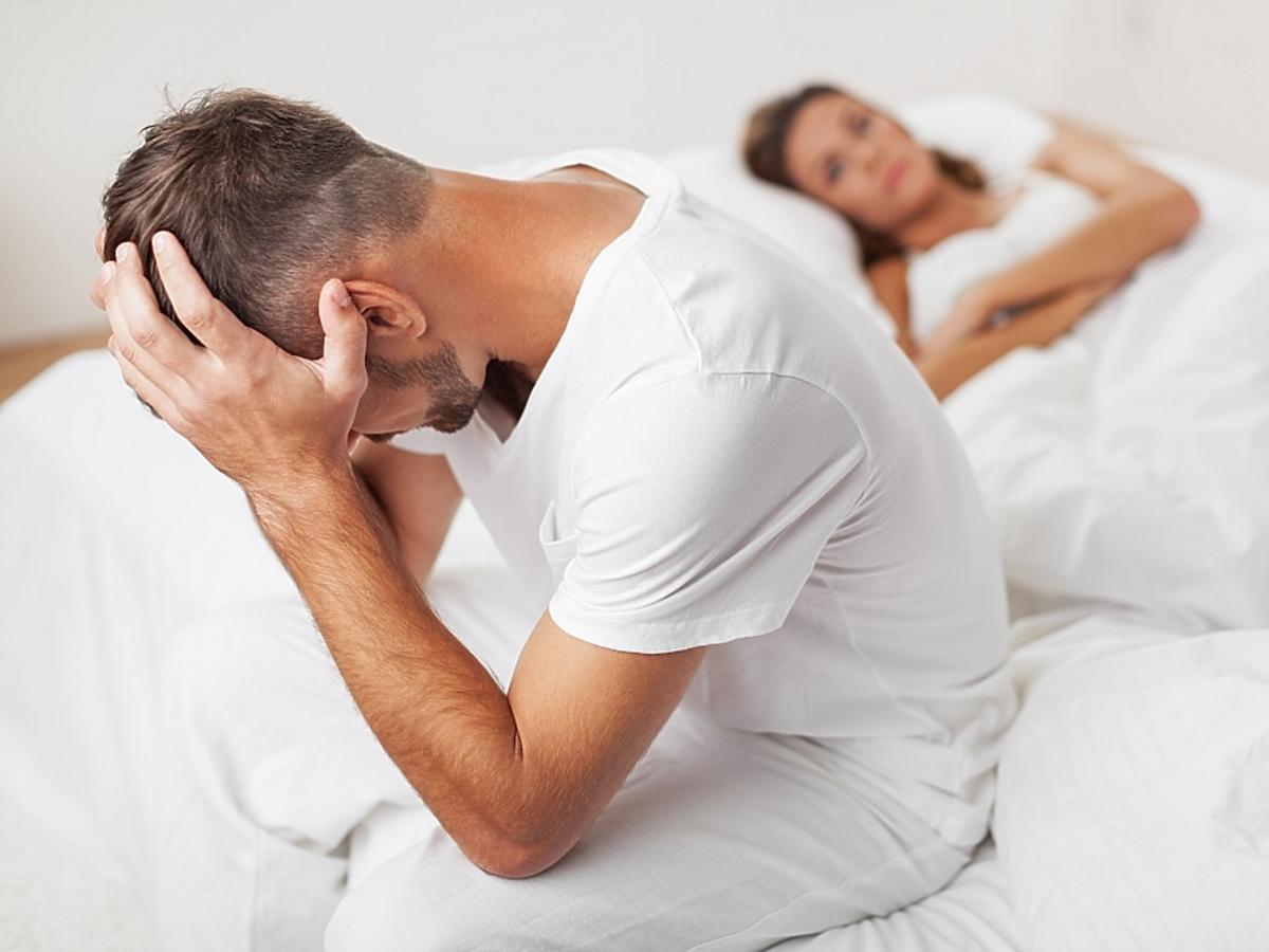 Mężczyzna siedzi załamany na łóżku