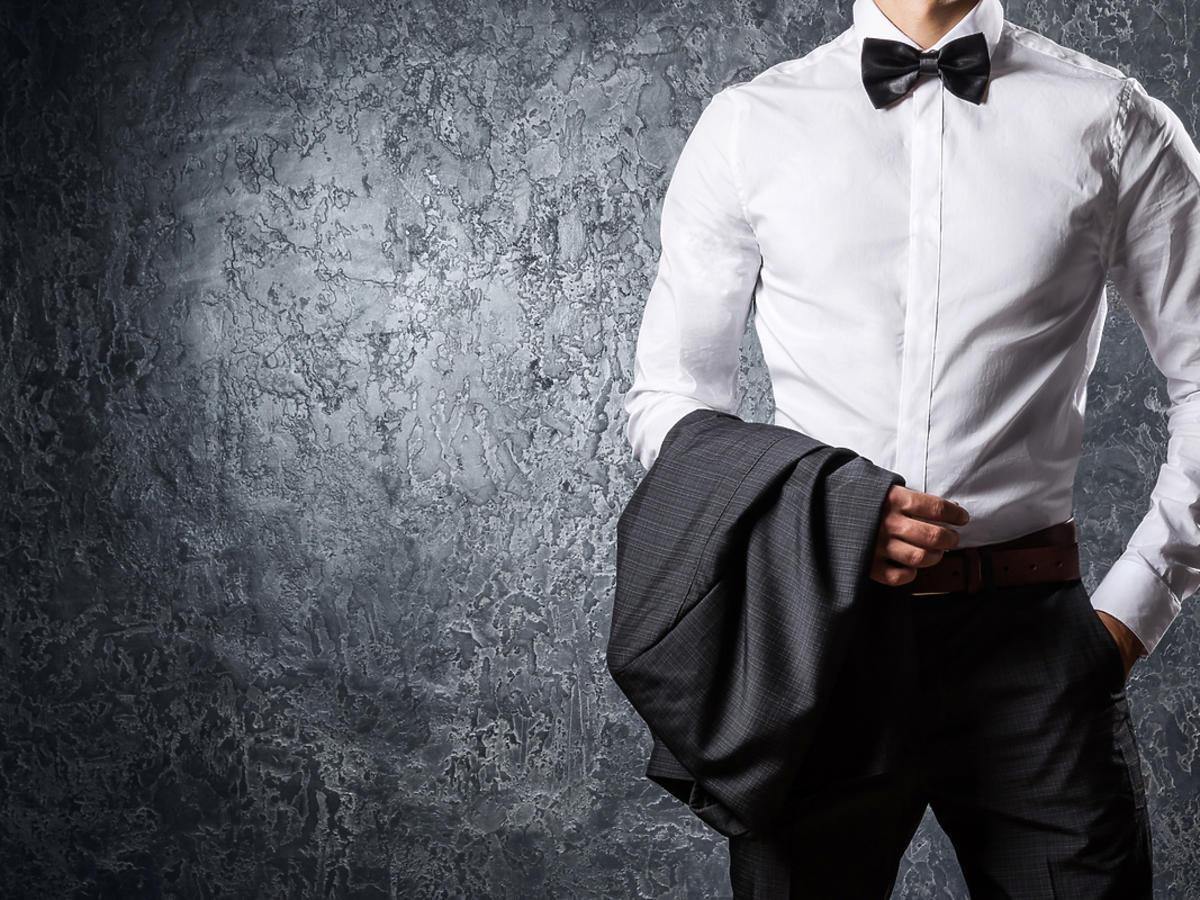 Mężczyzna stoi pod ścianą elegancko ubrany.