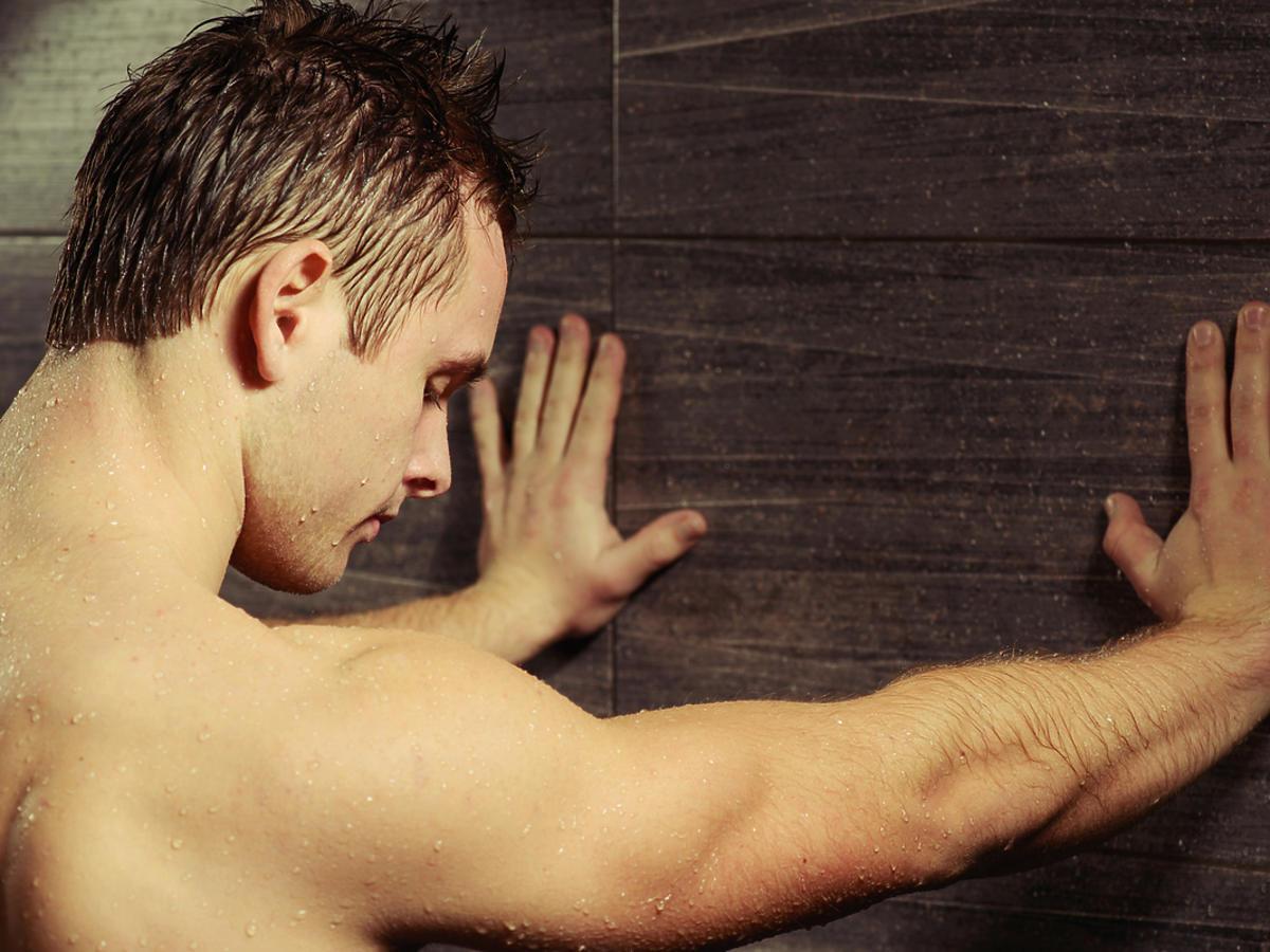 Mężczyzna stojący pod prysznicem