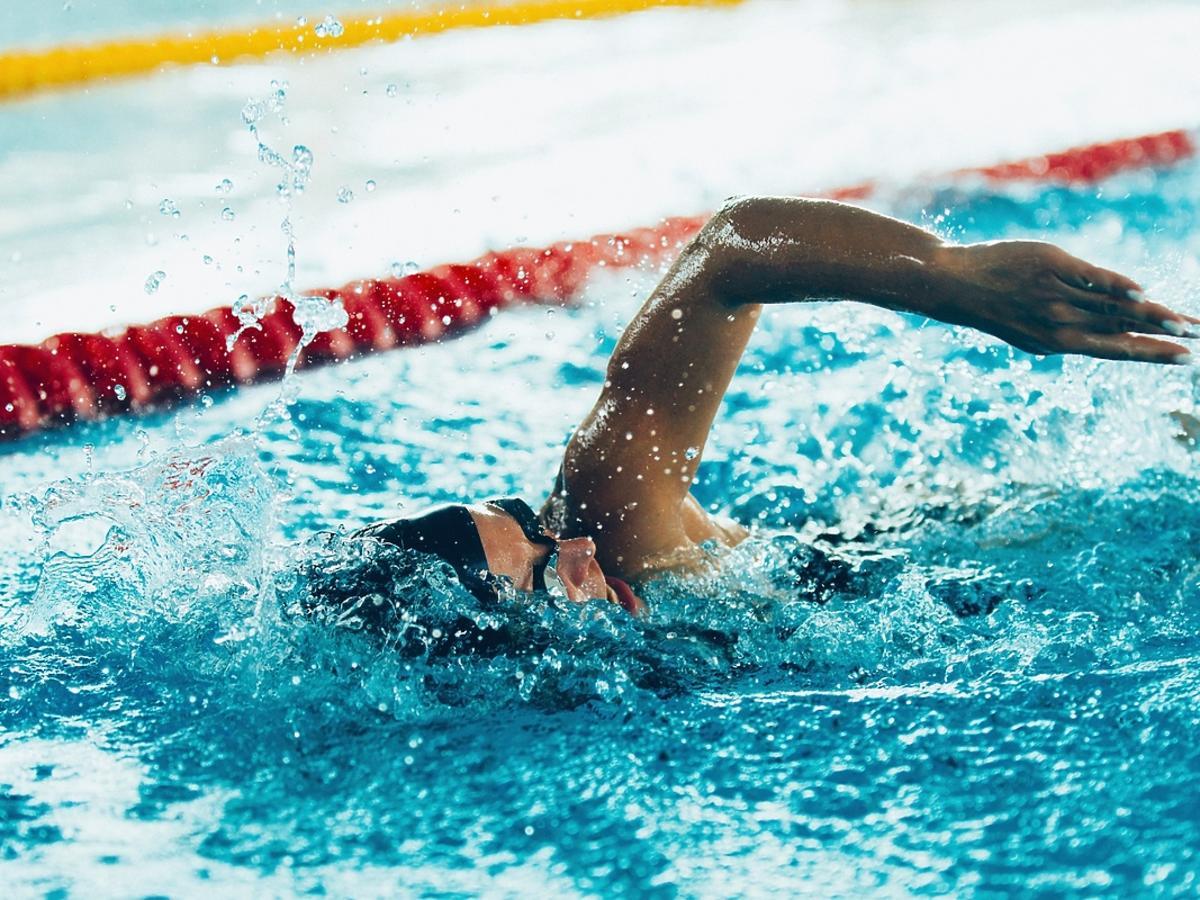 Mężczyzna trenuje na pływalni.