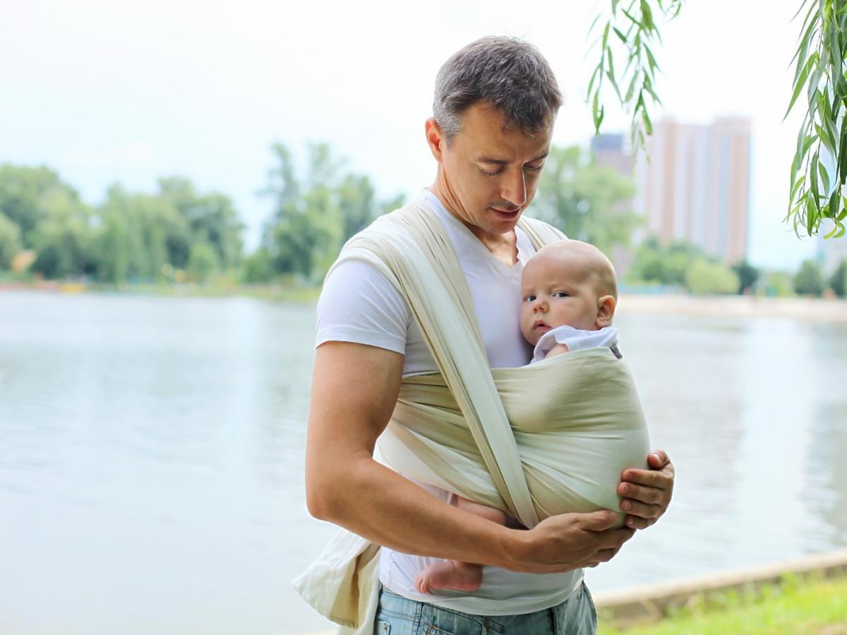 Mężczyzna trzyma dziecko w chuście do noszenia dzieci