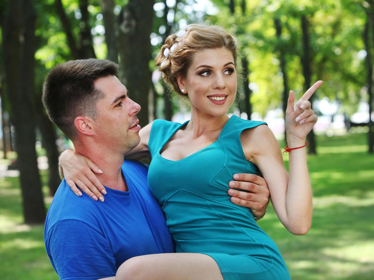 Mężczyzna trzyma kobietę na rękach. Są w parku.