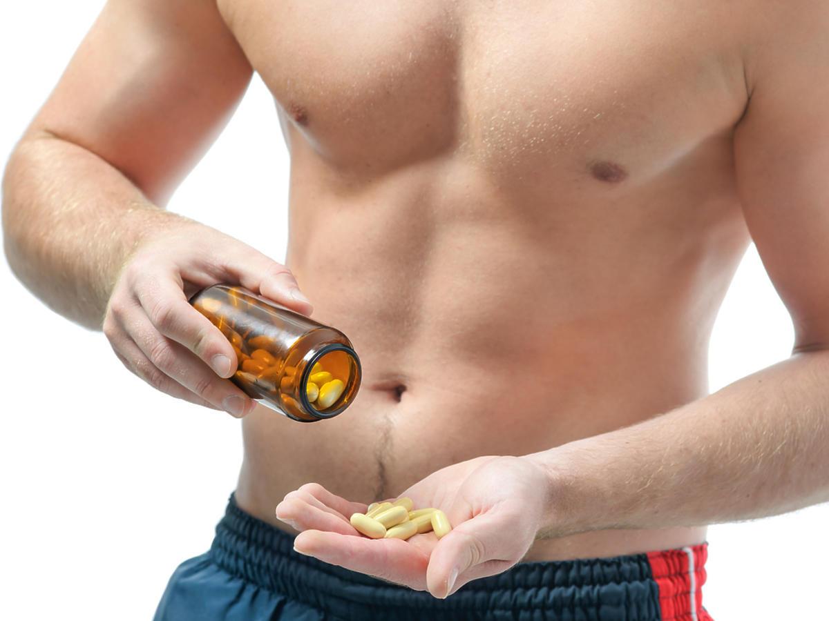 Mężczyzna trzyma pojemnik z tabletkami